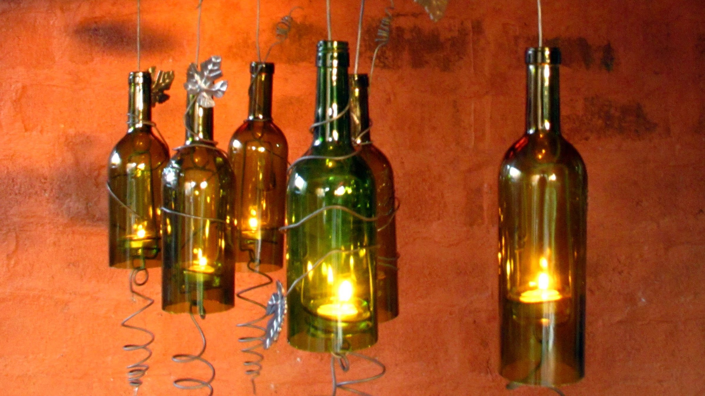 diy recycled wine bottles made into a hurricane candle holder