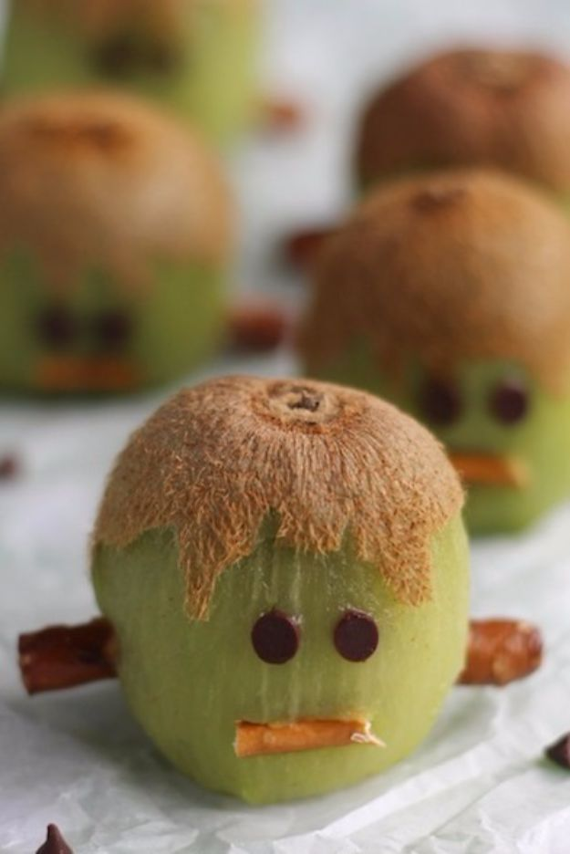 Healthy Halloween Party Snacks - Frankenstein Kiwis - Healthy Ideas for Kids for School, Teens and Adults - Easy and Quick Recipes and Idea for Dips, Chips, Spooky Cookies and Treats - Appetizers and Finger Foods Made With Vegetables, No Candy, Cheap Food, Scary DIY Party Foods With Step by Step Tutorials #halloween #halloweenrecipes #halloweenparty