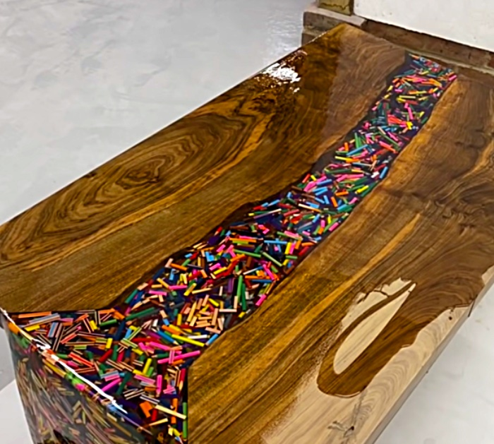 Make and epoxy and wood table with thousands of colored pencils