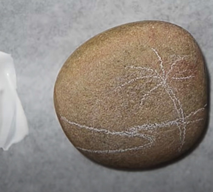 Paint a small rock with gesso and make a beach scene