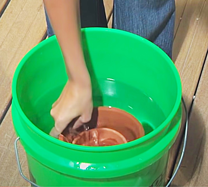 Soak terracotta pots to drill holes for a fountain